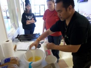 Freddy adds milk while Jerilynn and Marie watch during an APP French toast cooking class.