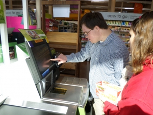 Aaron gets assistance from staff in operating a self-checkout machine.
